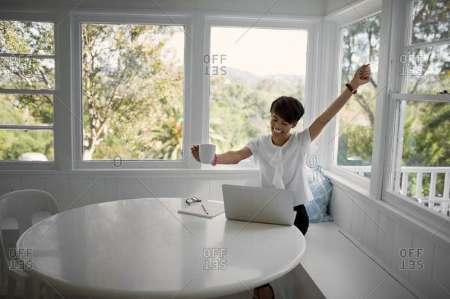 Young woman celebrating after receiving good news on her laptop