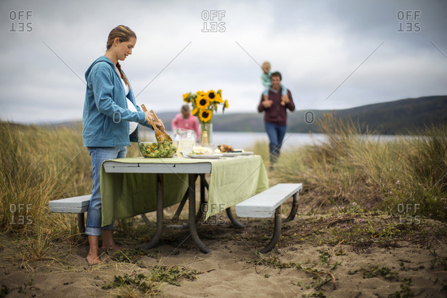 Family preparing a picnic table for an outdoor lakeside meal