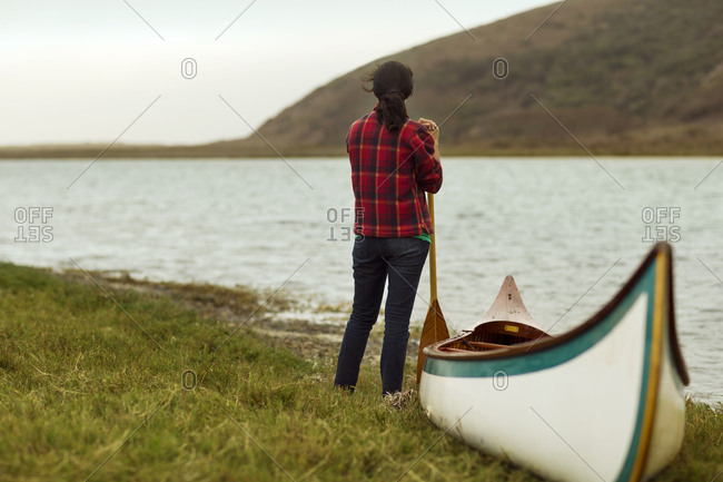 Canoeist looking out at a tranquil lake
