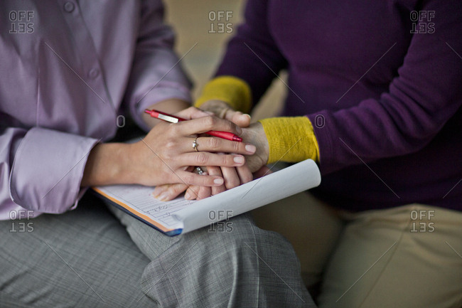 Two women holding hands after signing a document