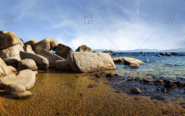 Boulders in shallow ocean waters