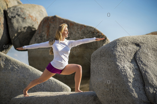 Young woman practicing yoga on a large rock