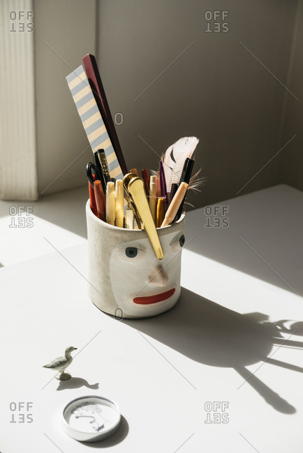 Cup with a face holding pens and other office supplies