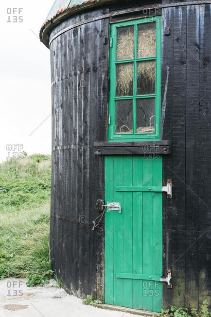 Black wooden building with green door and window