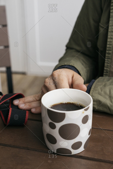 Man drinking coffee from a mug with polka dots