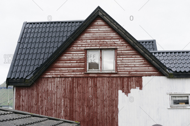 Red house in Denmark in the process of being painted white