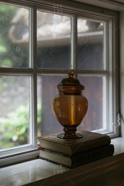 Apothecary jar on a stack of books by a window