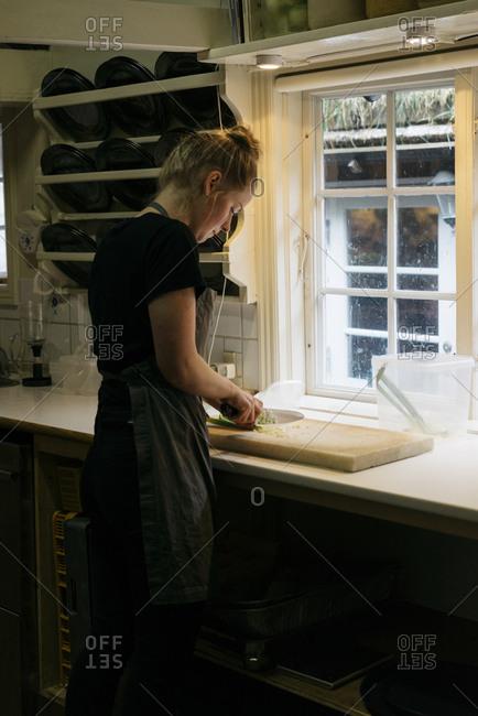 Torshavn, Faroe Islands, Denmark - August 30, 2016: Woman chopping vegetables in a kitchen