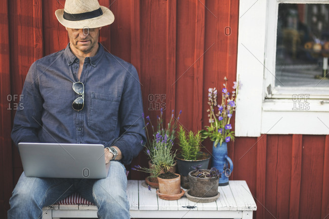 Man using laptop while sitting on bench by potted plants in back yard