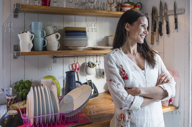 Happy woman standing by counter with arms crossed in kitchen at home
