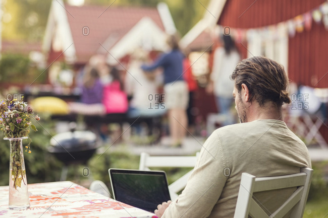 Rear view of man using laptop while sitting on chair in back yard