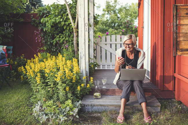 Cheerful woman using mobile phone and laptop while sitting in back yard on sunny day