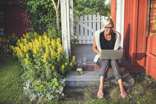 Woman using laptop while sitting in back yard on sunny day