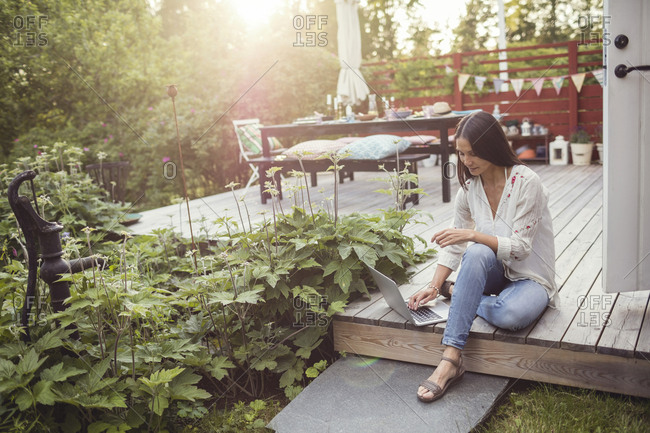 High angle view of woman using laptop while sitting on floorboard at patio in back yard