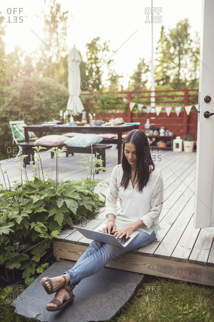 Woman using laptop while sitting on floorboard at patio in back yard