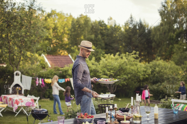 Man carrying plates by dining table in back yard during garden party