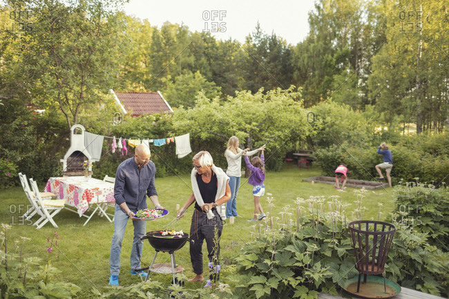Man and woman cooking vegetables on barbecue grill with kids enjoying garden party
