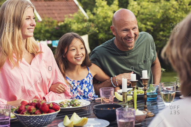 Playful man sitting with girls at dining table in back yard