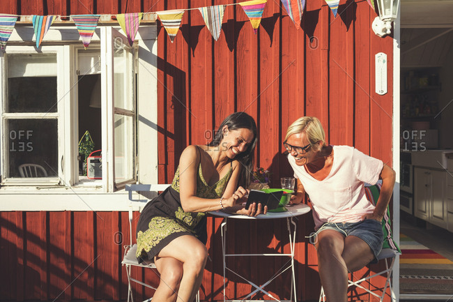 Happy woman showing mobile phone to female friend while sitting in back yard on sunny day