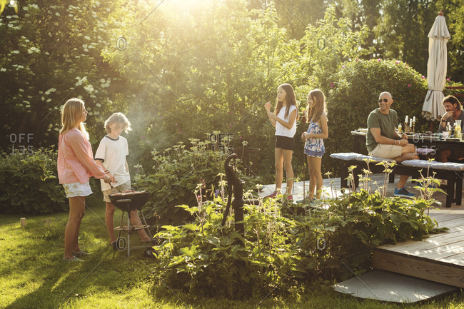 People enjoying summer during garden party on sunny day