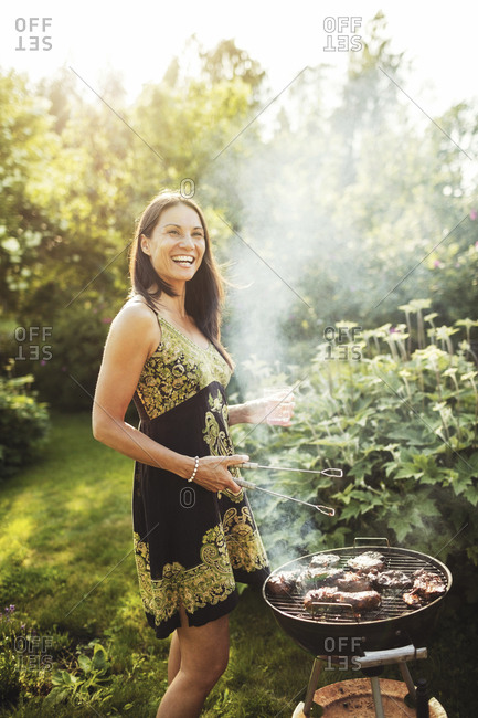 Happy woman standing by barbecue in back yard