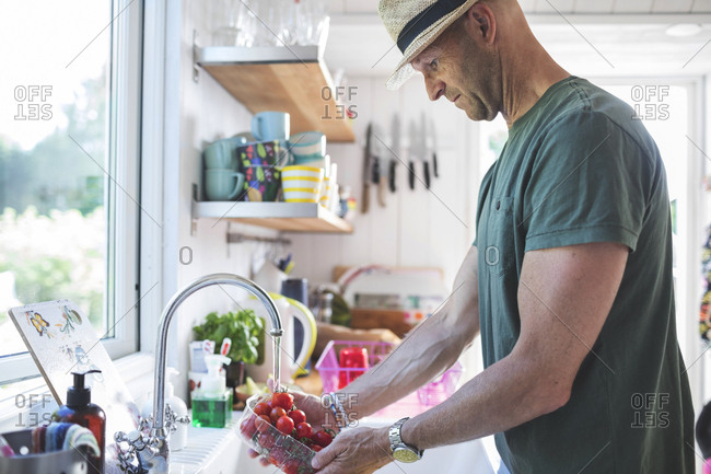 Side view of man washing cherry tomatoes under faucet in kitchen at home