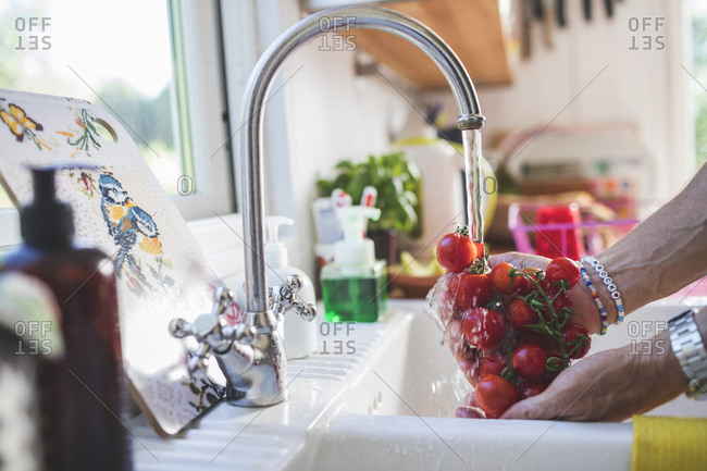 Cropped hands of man washing fresh cherry tomatoes under faucet in kitchen at home