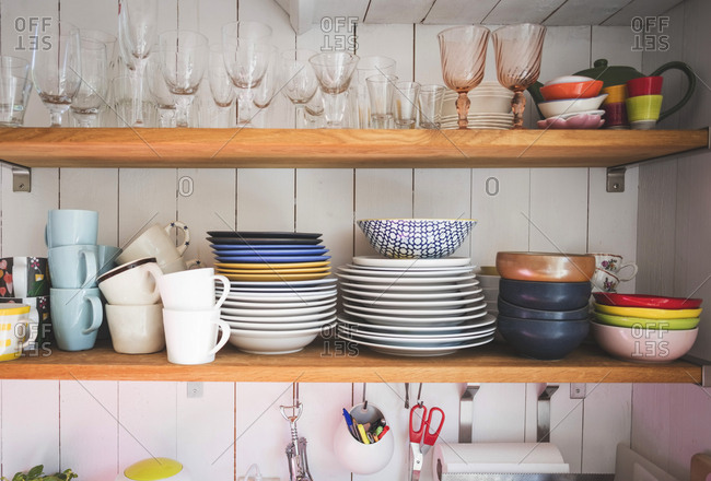 Crockery and drinking glasses on shelves in kitchen at home