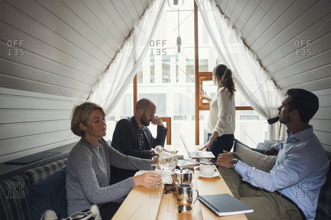 Business people working at table while female colleague opening office window