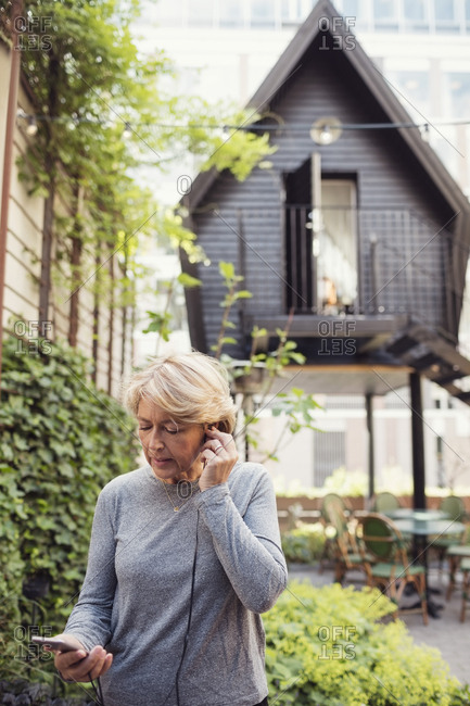 Mature businesswoman using in-ear headphones and smart phone at office yard
