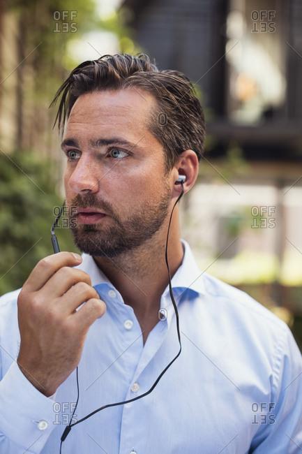 Confident businessman talking through in-ear headphones at office yard