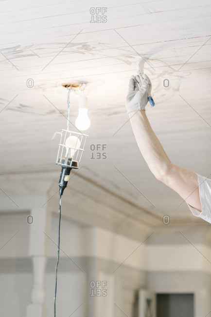Cropped image of painter painting ceiling at home