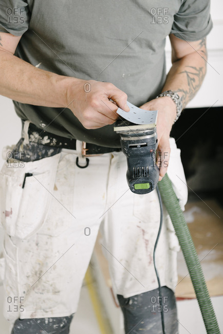 Midsection of house painter preparing sander