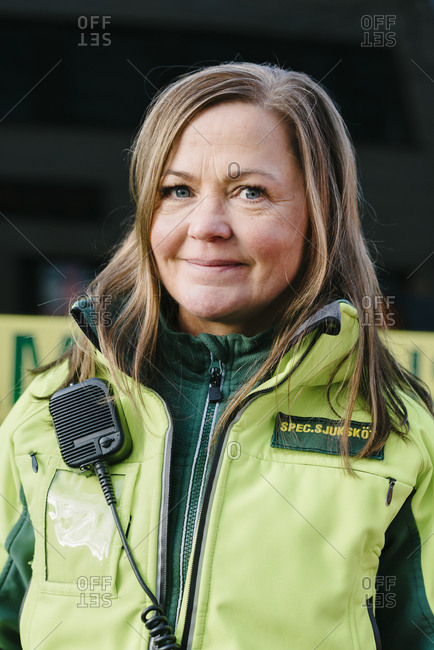 Portrait of smiling paramedic in reflective clothing standing against ambulance