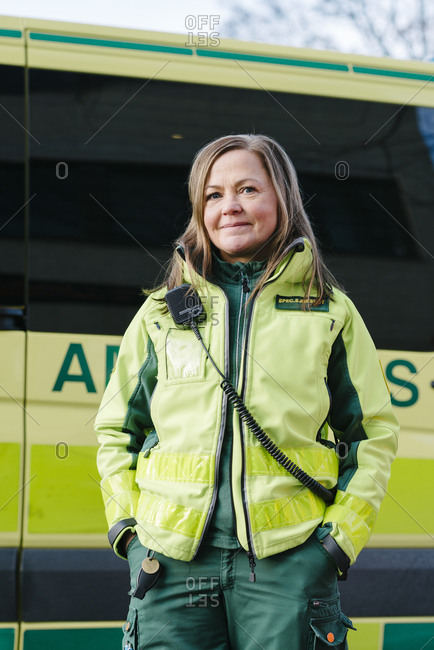 Portrait of confident paramedic in reflective clothing standing against ambulance
