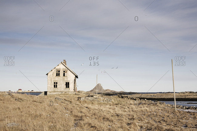 Abandoned building on field against sky on sunny day
