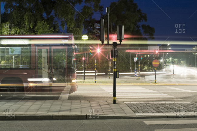 Bus by light trails on street in city at night