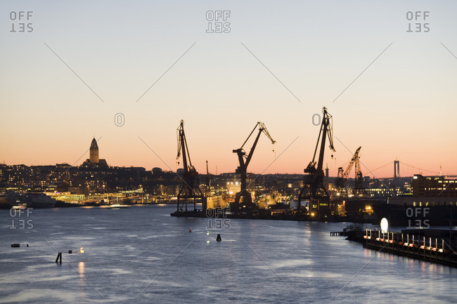 Silhouette cranes at commercial dock by Gota Canal against clear sky during sunset