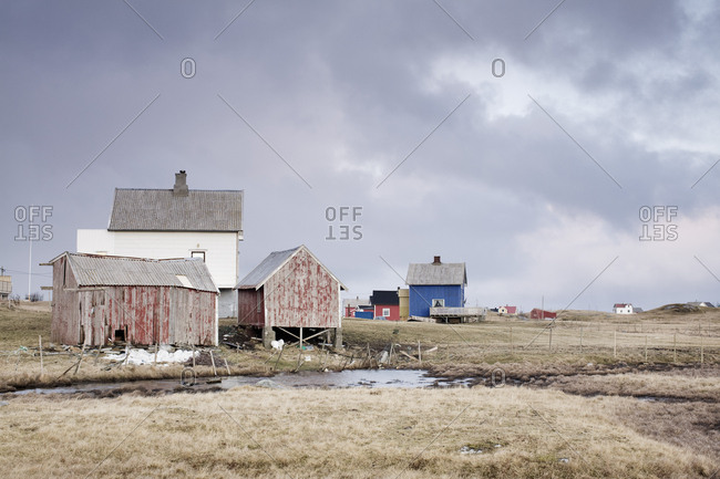 Old houses on field against cloudy sky