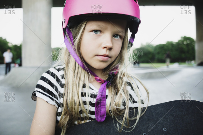 Portrait of girl wearing pink helmet holding skateboard at park