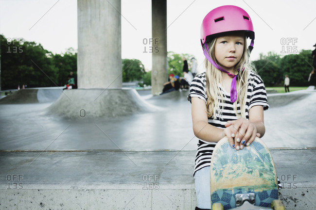Portrait of girl with skateboard sitting at park