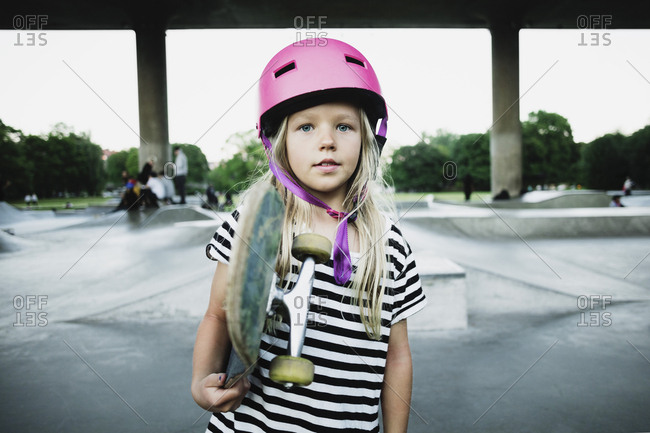 Portrait of girl holding skateboard while standing at park