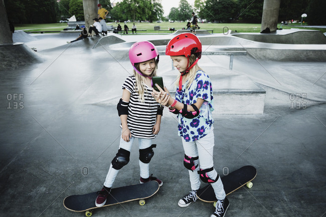 Girl showing mobile phone to friend while standing at skateboard park
