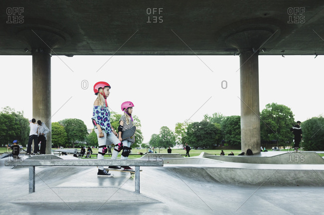 Side view of friends standing at skateboard park against clear sky