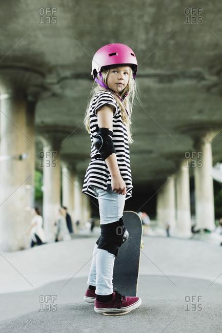 Full length of confident girl standing with skateboard at park
