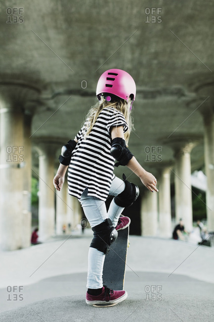Rear view of girl performing stunt with skateboard at park