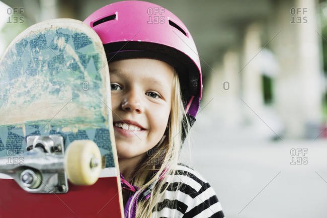Portrait of happy girl with skateboard at park