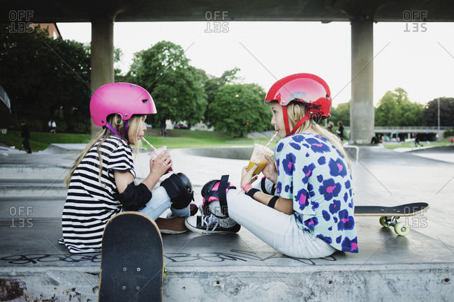 Friends drinking juice while sitting at skateboard park