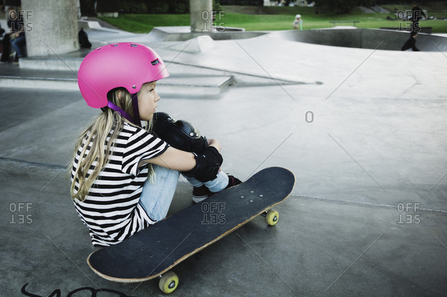 Thoughtful girl wearing pink helmet sitting at skateboard park