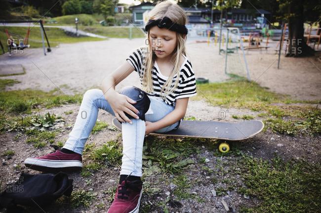 Girl tying kneepad while sitting on skateboard at park